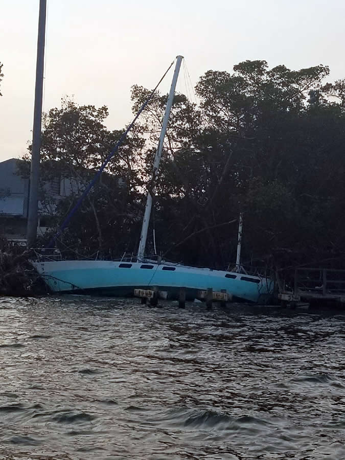 Sailboat listing up against shore.